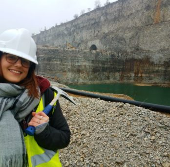 Geopath mentor sam in a quarry with a rock hammer in hand